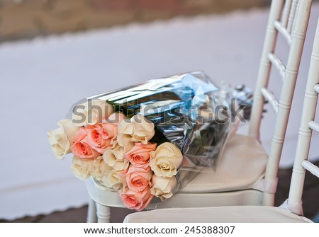 Gift rose bouquet lying on a chair near the wedding carpet. Flowers in cellophane wrapper - stock photo
