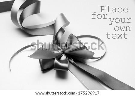 Gift satin ribbon bow in grey shadows - stock photo