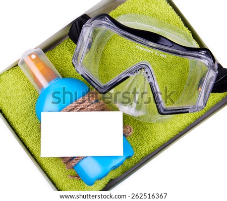 Gift set - green towel, blue bottle of suntan spray and professional dive mask in paper box. Decorated with rope. White paper card for your text on the bottle. Isolated - stock photo