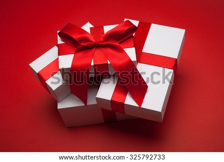 Gift with red bow on red background - stock photo