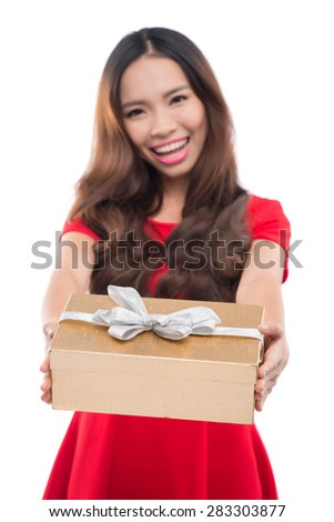Gift woman in red smiling showing present. Beautiful Asian / Caucasian girl isolated on white background. Shallow depth of field, focus on gift - stock photo