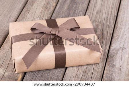 Gift wrapped in brown paper, ribbon and bow on a wood background - stock photo