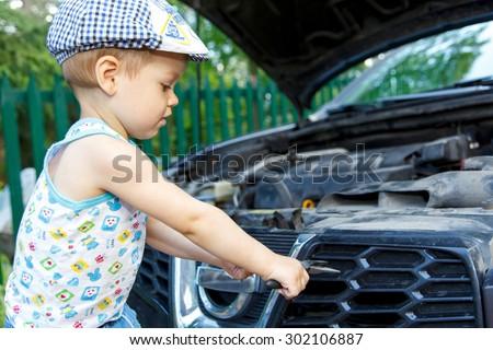 Gifted kid repairing car engine - stock photo