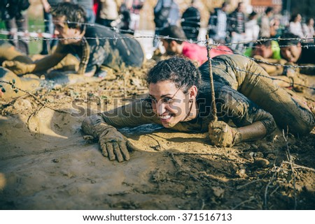 GIJON, SPAIN - JANUARY 31, 2016: Farinato Race event, a extreme obstacle race, celebrated in Gijon, Spain, on January 31, 2016. Portrait of woman crawling under a barbed wire in a test of the race. - stock photo