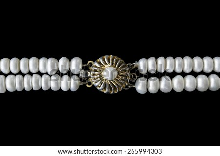 Gilded vintage clasp on pearl necklace isolated over black - stock photo