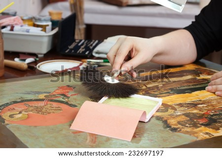 gilding of ancient icon with gold leaf in workshop - stock photo