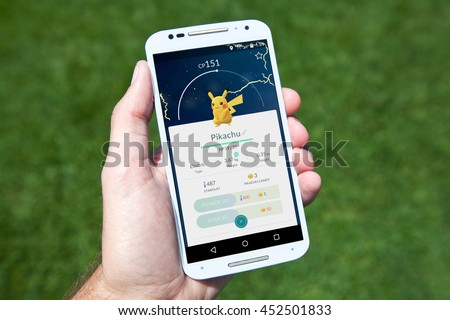 "GILROY, CALIFORNIA - JULY 14, 2016: A person playing the hit smartphone app ""Pokemon GO"" views a captured Pikachu while searching outside for new Pokemon. - stock photo"
