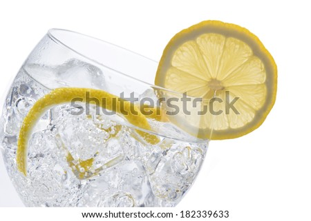 Gin and tonic in a balloon glass garnished with lemon and isolated over awhite background - stock photo