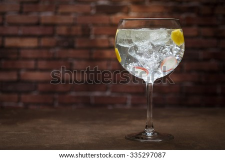 Gin and tonic on a wooden table with bricks background - stock photo