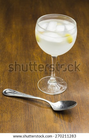 Gin and tonic with green olives and ice on a bar table - stock photo
