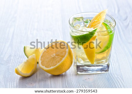 gin and tonic with lemon , lime and ice on wooden table - stock photo