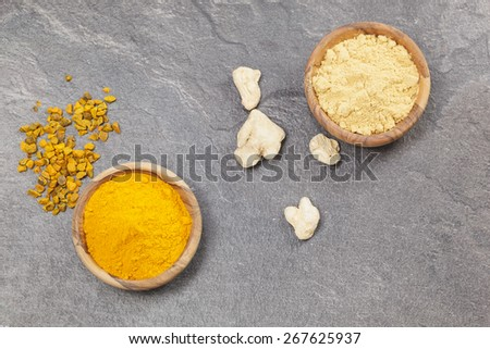 Ginger And Turmeric. Ginger powder and root  and turmeric pieces and powder in olive wood bowls over dark granite table.  Macro photograph, selective focus, focus on turmeric. - stock photo