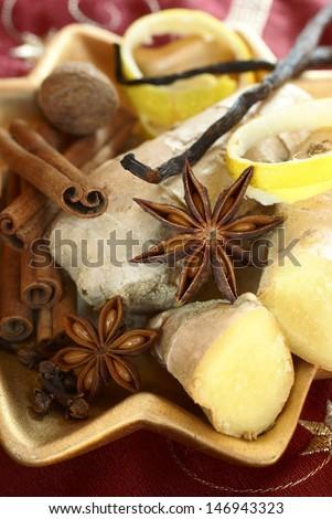Ginger, anise stars, cinnamon sticks, nutmeg, clove, vanilla beans and lemon peel on decorative plate. - stock photo