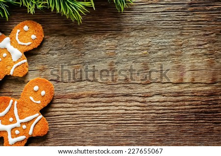 ginger biscuits and a branch of a Christmas tree on a dark wood background. tinting. selective focus - stock photo