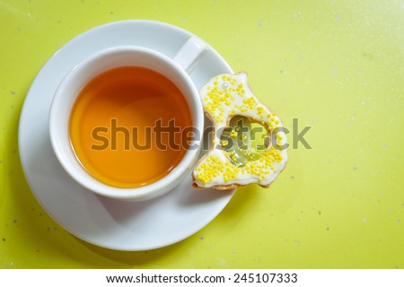 Ginger cookie and cup of tea on green background - stock photo