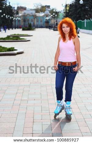 Ginger girl on roller skates in Mariinsky Park in Kiev - stock photo