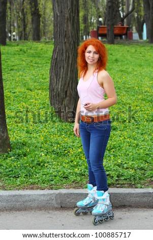 Ginger girl on roller skates listening to music in the park - stock photo