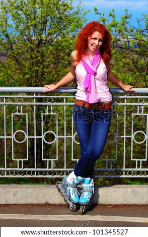 Ginger girl on roller skates with her legs crossed in Mariinsky Park, Kiev - stock photo
