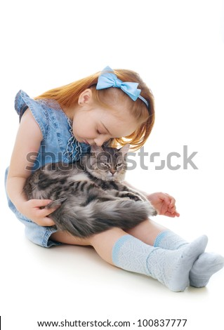 Ginger girl sits on the floor holding a cat on her knees - stock photo