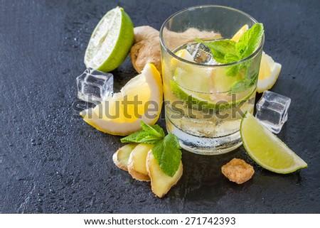 Ginger lemonade and ingredients - ginger, lemon, lime, mint, sugar, ice, dark stone background, water drops - stock photo