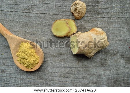 ginger root,ground ginger on wooden background - stock photo