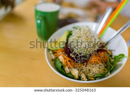 ginger sesame soy baked tofu, shredded beets & carrots, on organic brown rice & spinach, topped with sprouts, pumpkin & sunflower seeds and a tahini garlic dressing - stock photo