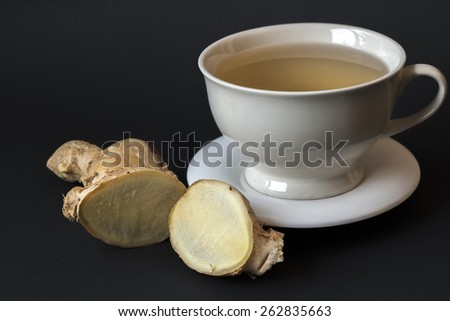 Ginger tea in white cup in studio black background setting - stock photo