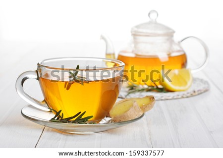 Ginger tea with lemon and rosemary in glass cup closeup. - stock photo