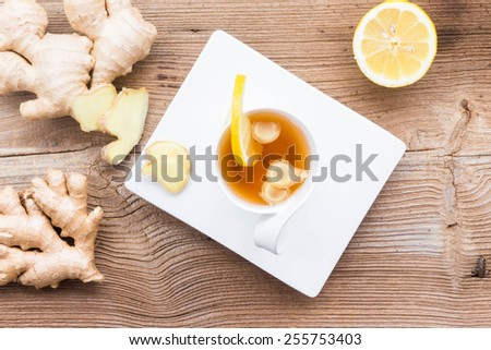 Ginger tea with lemon on white cap on wooden table, top view - stock photo