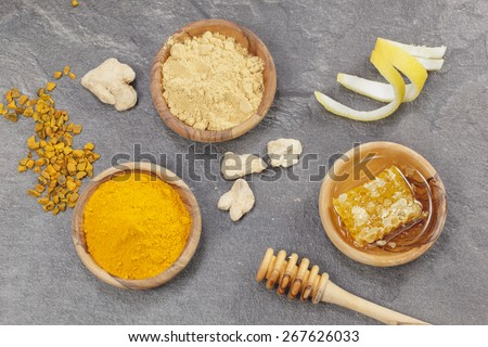 Ginger, Turmeric,lemon  and honeycomb. Ginger powder, root  and turmeric pieces, powder and honeycomb in olive wood bowls over dark granite table. Macro photograph, selective focus - stock photo