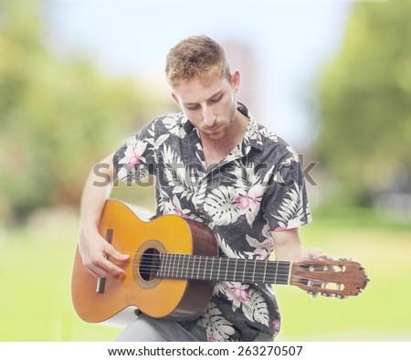ginger young man with hawaiian shirt playing the guitar - stock photo