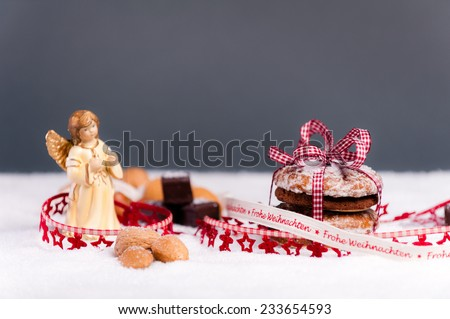 Gingerbread and dominoes with nuts on artificial snow in front of a grey background. In a festive decoration with an angel on the left. - stock photo