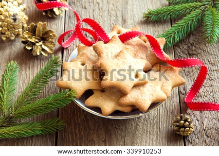 Gingerbread Christmas cookies on rustic wooden table with golden pine cones, fir branches and red ribbon for winter holidays - stock photo