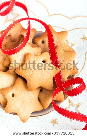 Gingerbread Christmas cookies on white napkin with stars and red ribbon for winter holidays - stock photo
