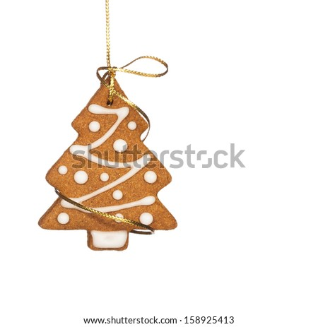 Gingerbread Christmas tree cookie hanging by golden string isolated on white. - stock photo