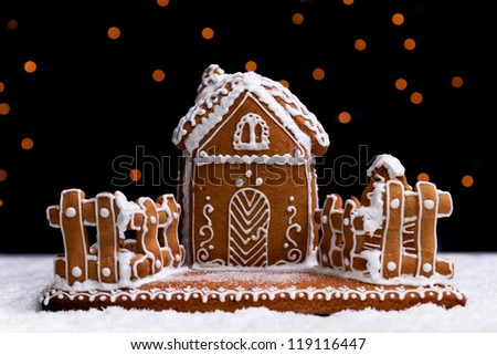 Gingerbread cookie house on dark background with blurry christmas lights - stock photo