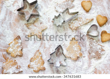 Gingerbread cookies and cutters on wooden pastry board after baking, top view. - stock photo