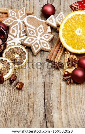 Gingerbread cookies, cinnamon sticks and christmas balls on wooden table. Xmas greetings. Copy space.  - stock photo