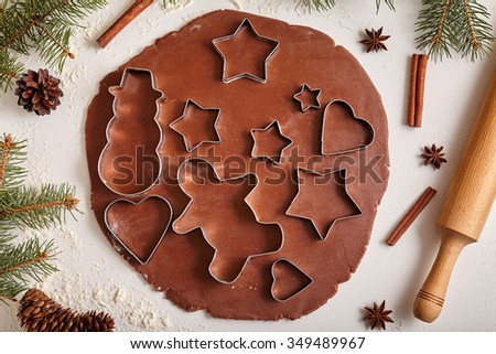 Gingerbread cookies dough preparation recipe with man shape, heart, fir trees, snowman and star forms, cinnamon rolling pin, flour on white kitchen table. Traditional homemade christmas dessert - stock photo