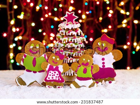 Gingerbread cookies family in front of christmas tree - holidays food setting - stock photo