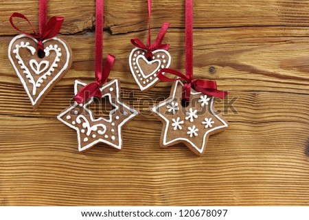 Gingerbread cookies hanging on wooden background. Christmas decoration. - stock photo