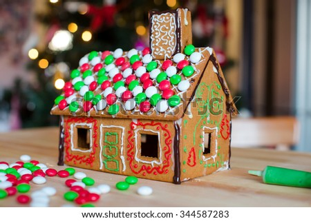 Gingerbread fairy house background of bright Christmas tree with garland - stock photo