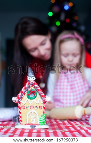Gingerbread fairy house decorated by colorful candies on a background of happy family - stock photo