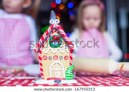 Gingerbread fairy house decorated by colorful candies on a background of little girls - stock photo