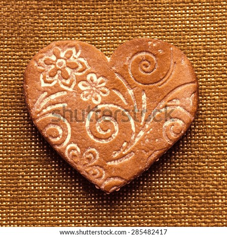 Gingerbread handmade ornaments in retro style in the shape of heart - sweet gifts for lovers. Christmas gingerbread heart with vintage texture. Homemade cakes for the Holidays on Valentine Day. - stock photo