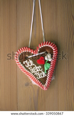 Gingerbread heart with wooden background - stock photo