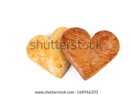 Gingerbread hearts on white background. One heart is dark and the other is light. - stock photo