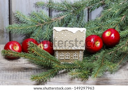 Gingerbread house on fir branch among red apples. - stock photo