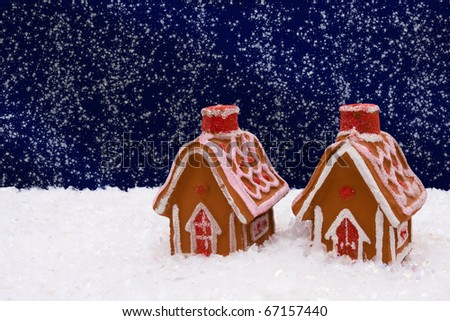 Gingerbread house on snow with a night sky background, winter time - stock photo