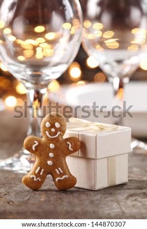 Gingerbread man and gift box on Christmas table. - stock photo